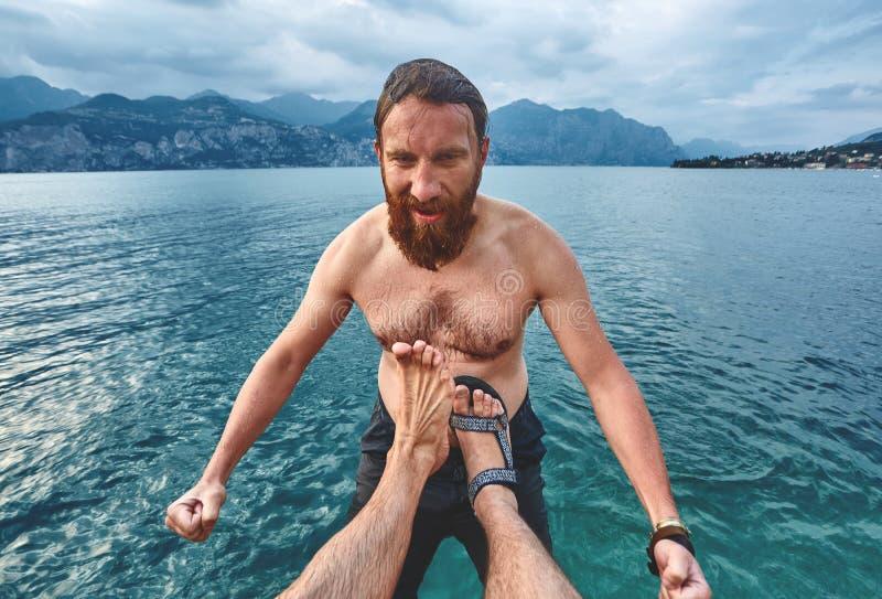 Der Mann wird in das Wasser vom Pier getreten stockbild