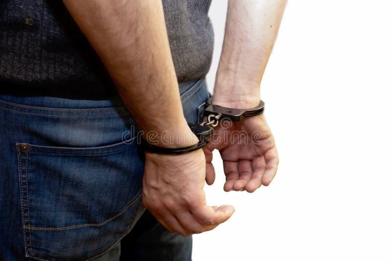Der Mann wird, seine Hände hinter seinem zurück, der gefangene Verbrecher mit Handschellen gefesselt stockfotos
