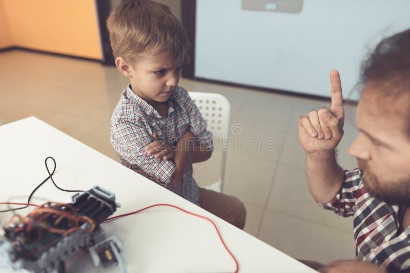 Der Mann züchtigt streng den Jungen für das Verderben des Roboters Die Jungenblickschmerzen am Mann lizenzfreie stockfotos
