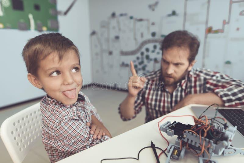 Der Mann züchtigt streng den Jungen für das Verderben des Roboters Der Junge abgewendet von dem Mann und dem Krächzen stockbilder