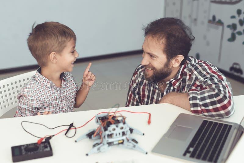 Der Mann züchtigt streng den Jungen für das Verderben des Roboters Der Junge züchtigt den Mann als Ausgleich lizenzfreies stockfoto