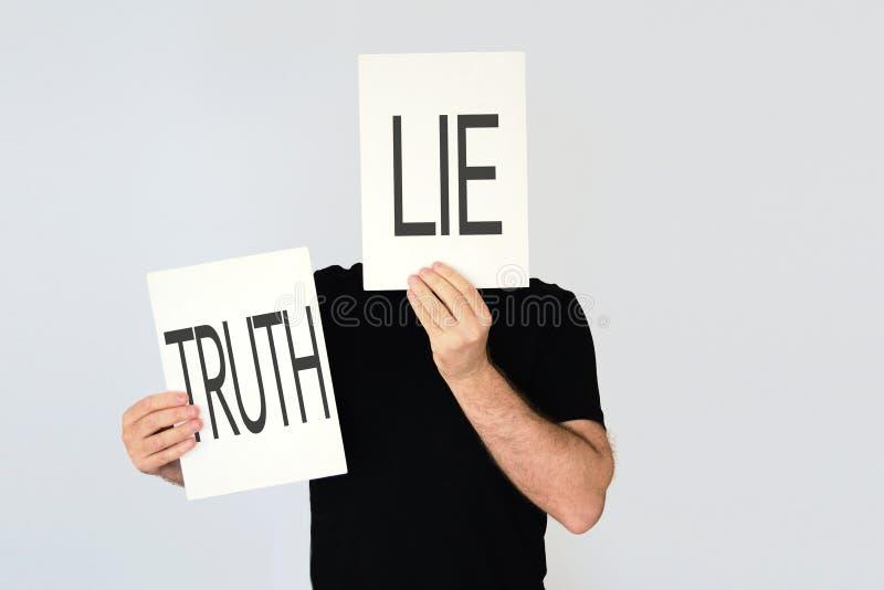 Der Mann, der zwei Karten mit den Wörtern hält, liegen und Wahrheit lizenzfreie stockfotografie