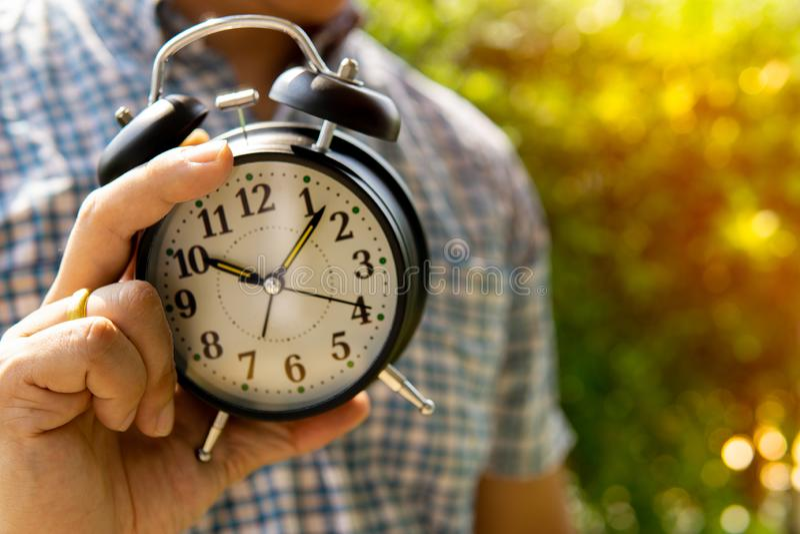 Der Mannholdingwecker im Sonnenlicht und Mann im Parkshowkonzept des Gebens von Zeit oder des Teilens der Zeit für etwas verwisch stockfotos