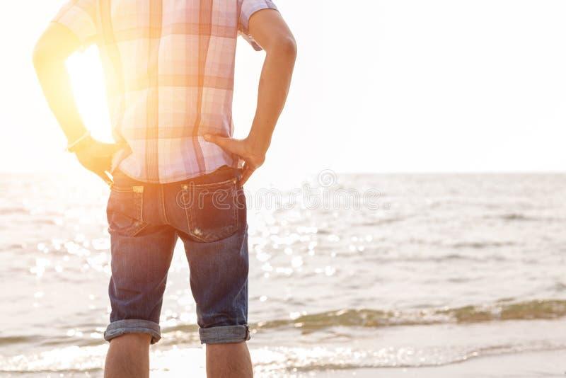 Der Mannstand auf dem Strand der Geschäftsabnutzungshut und Entspannung stockfotografie