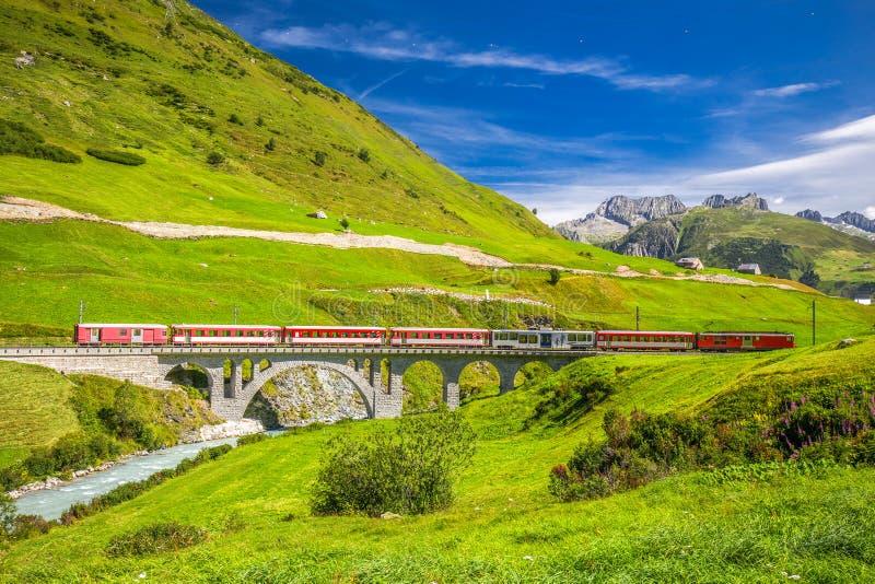 Der Matterhorn- - Gotthard- - Bahn-Zug auf der Viaduktbrücke nahe Andermatt in den Schweizer Alpen stockfotos