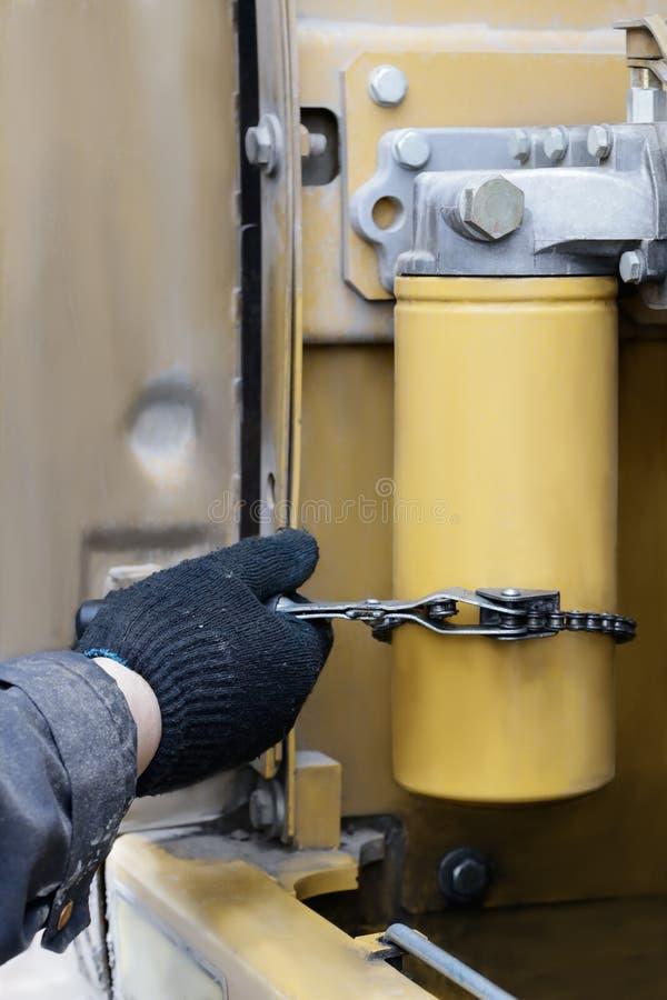 Der Mechaniker ersetzte den Ölfilter für die feine Filtration des Motoröls durch Saisonwartung stockbilder