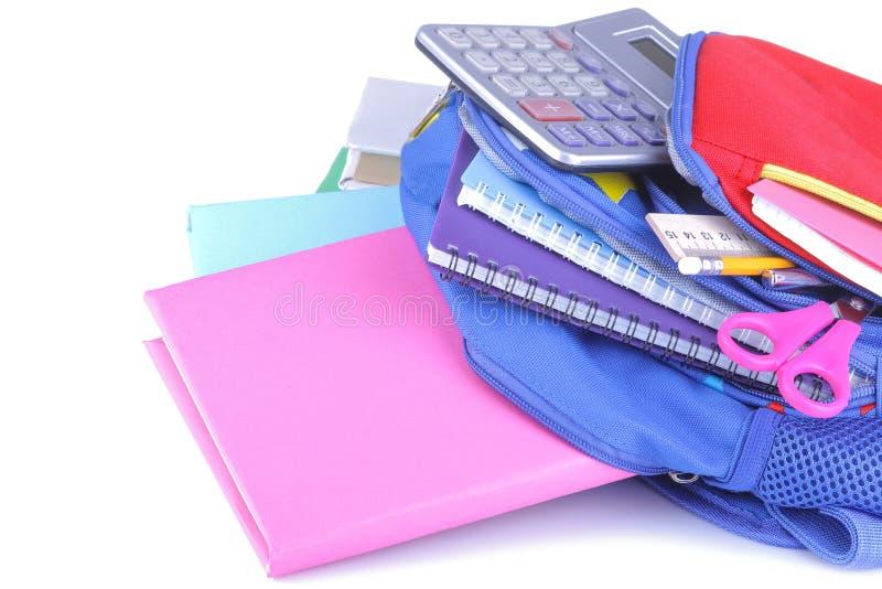 Der mehrfarbige Schulbedarf, der aus einem Rucksack auf einem Weiß heraus fällt, lokalisierte Hintergrund lizenzfreie stockbilder