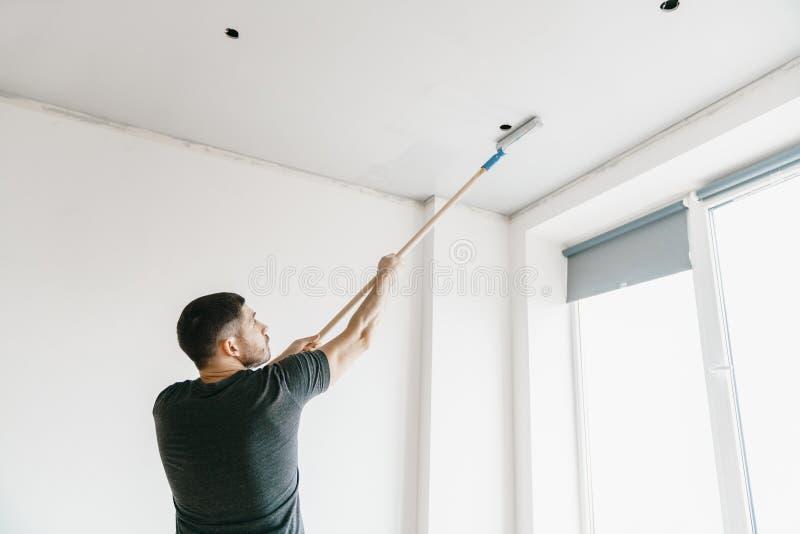 Der Meister in einem Grau T-Shirt malt die Decke mit einer Rolle in der grauen Farbe in seiner Wohnung stockfoto