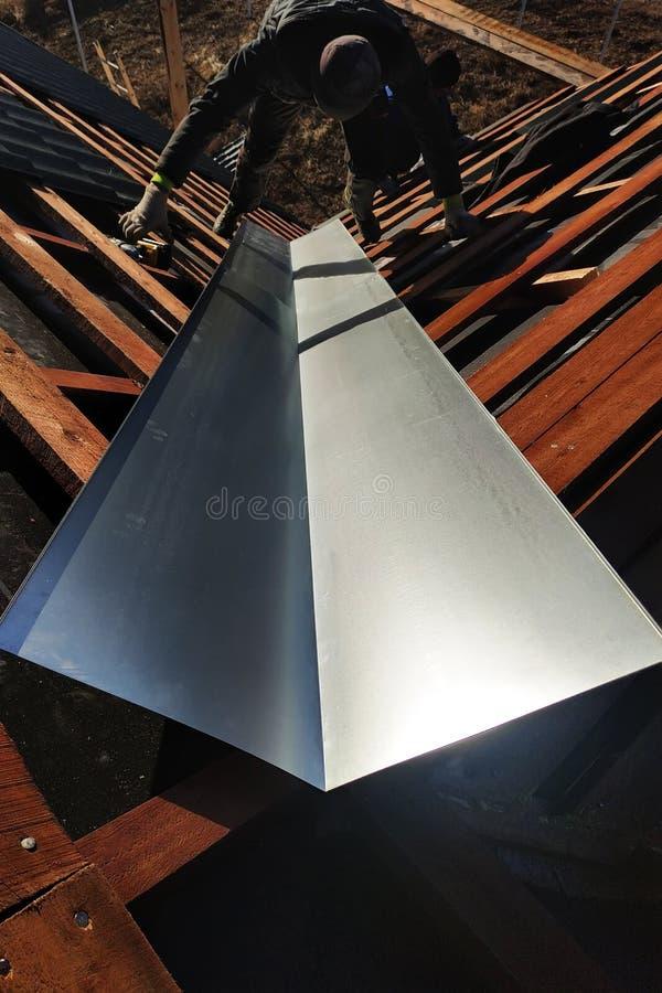 Der Meister führt die Installation eines metallischen Blattes am Brechungspunkt des Dachs zum Abwasser während des Regens durch lizenzfreie stockbilder