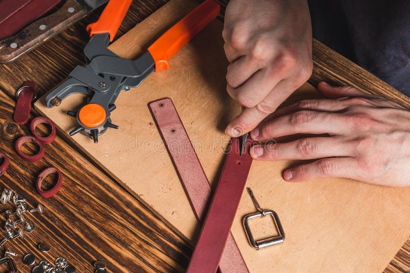 Der Meister hält in seiner Hand eine Ahle und das Arbeiten mit Leder Auf braunem Holztisch zerstreute mit Werkzeugen und Zubehör lizenzfreie stockbilder