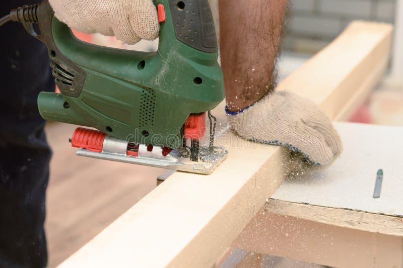 Der Meister sägt einen Holzbalken lizenzfreies stockbild