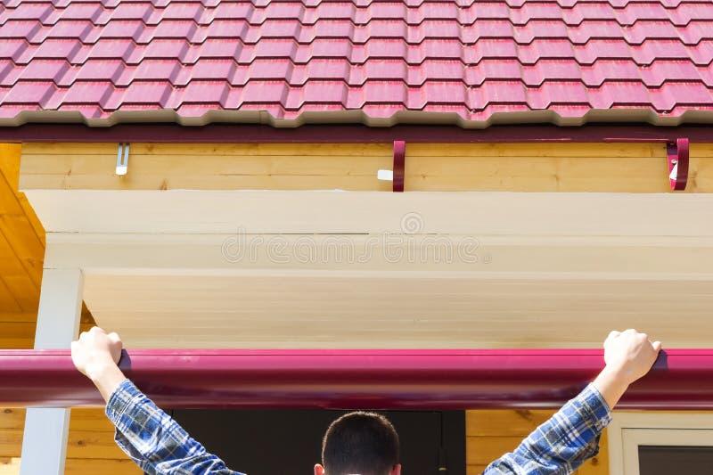 Der Meister versucht an das Gesims zum Dach stockfotografie