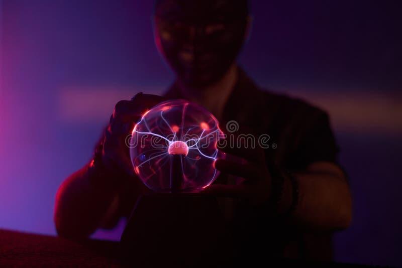 Der Mensch berührt den Plasma-Globus lizenzfreies stockfoto