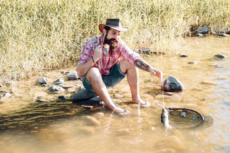Der Mensch entspannt und fischt am Seeufer Hobby Fischer mit Angeln und Fisch Der Mensch am Flussufer genießt eine ruhige idyllis lizenzfreie stockfotos