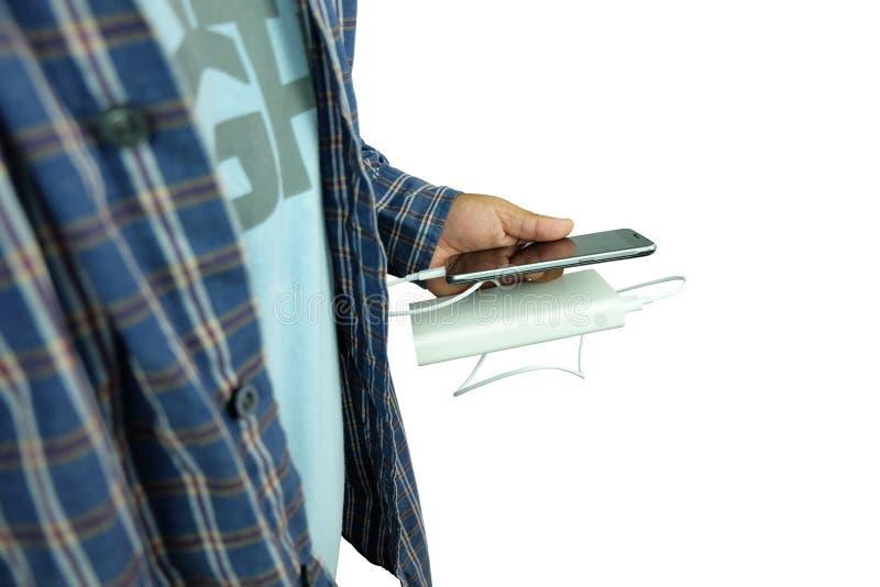 Der Mensch hält Smartphone lädt mit Backup-Batterie oder Strombank, die auf weiß isoliert ist lizenzfreie stockfotografie
