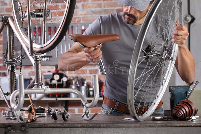 Der Mensch repariert das Vintage-Fahrrad in der Werkstatt auf der Werkbank mit Werkzeugen, Deuy-Konzept stockfotografie
