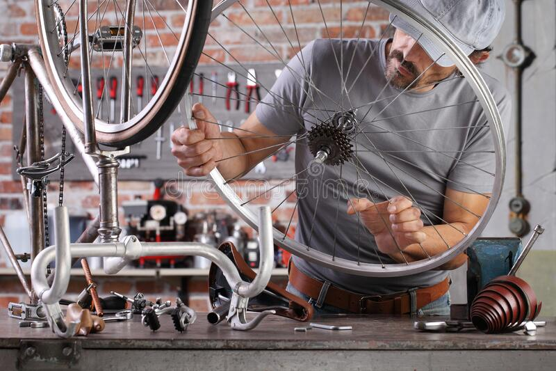 Der Mensch repariert das Vintage-Fahrrad in der Werkstatt auf der Werkbank mit Werkzeugen, Deuy-Konzept stockfoto