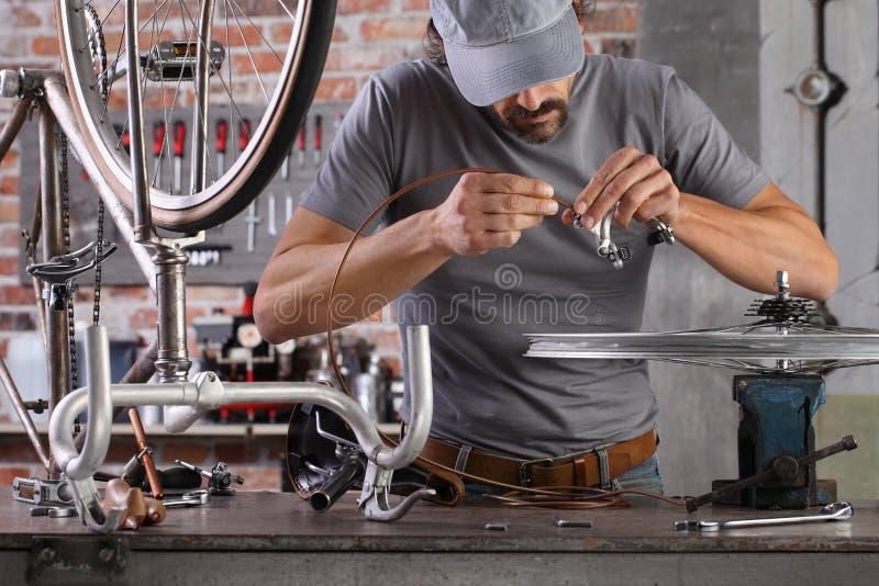 Der Mensch repariert das Vintage-Fahrrad in der Werkstatt auf der Werkbank mit Werkzeugen, Deuy-Konzept stockbilder