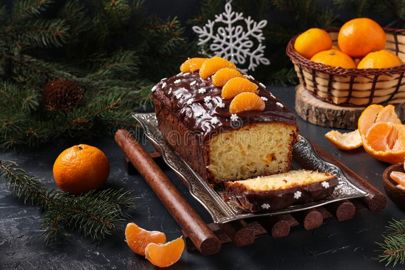Der mit Schokoladenglasur bedeckte Cupcake mit Tangerinen befindet sich im Neujahrsuntergrund, das festliche Stillleben lizenzfreies stockfoto