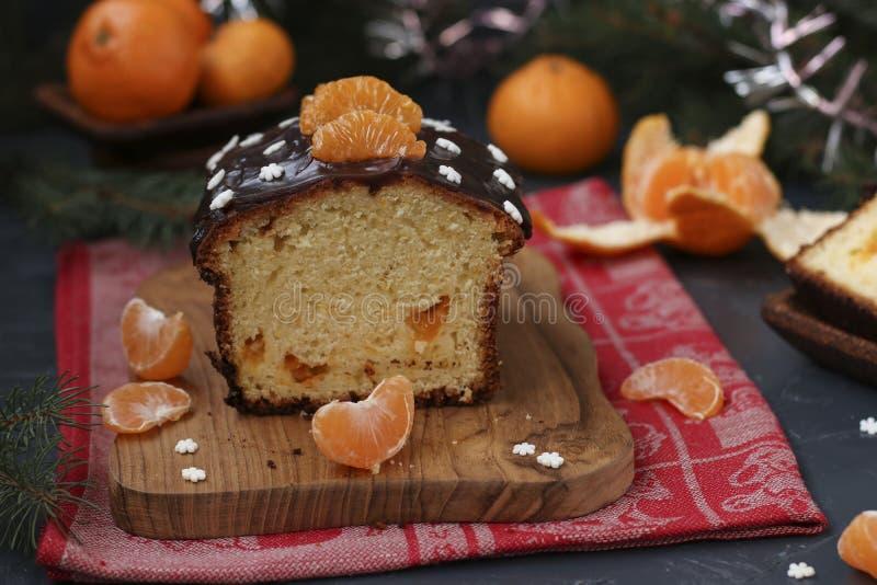 Der mit Schokoladenglasur bedeckte Cupcake mit Tangerinen befindet sich im Neujahrsuntergrund, das festliche Stillleben stockbilder