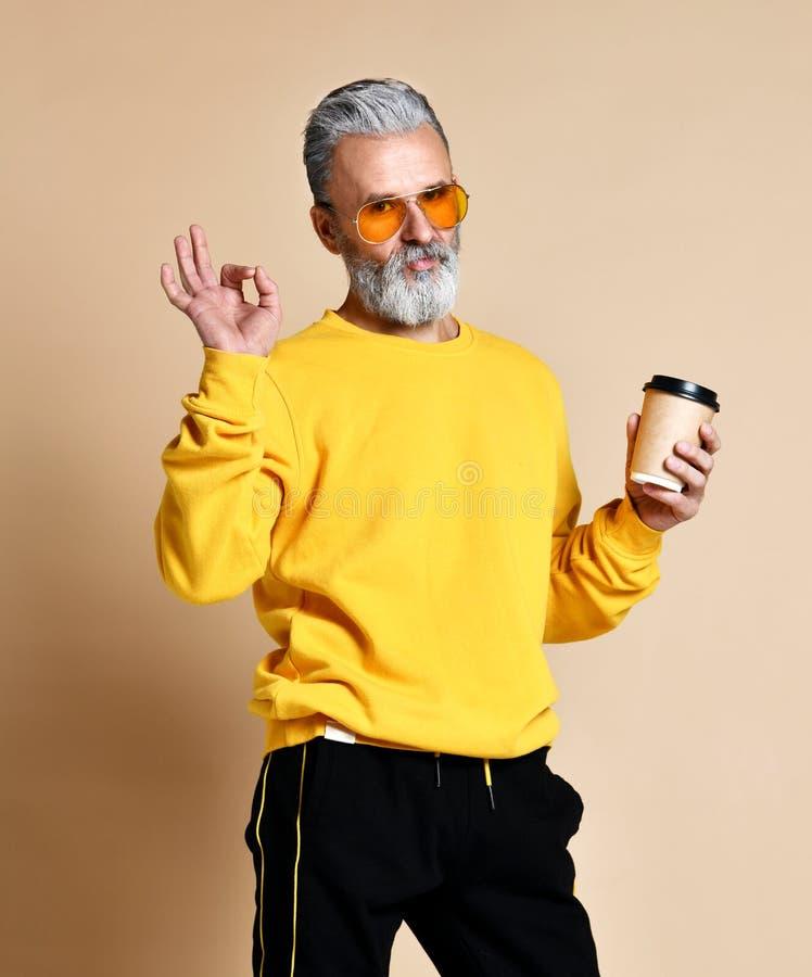 Der moderne Mannsenior, der Kamera, Kappe mit Kaffee in den Armen habend betrachtet und zeigt ein Zeichen-O.K. mit seinen Fingern lizenzfreies stockfoto