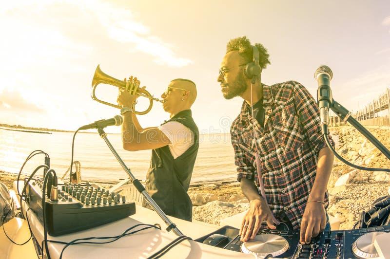 Der modische Hippie DJ, der Sommer spielt, schlägt am Sonnenuntergangstrandfest stockfotos