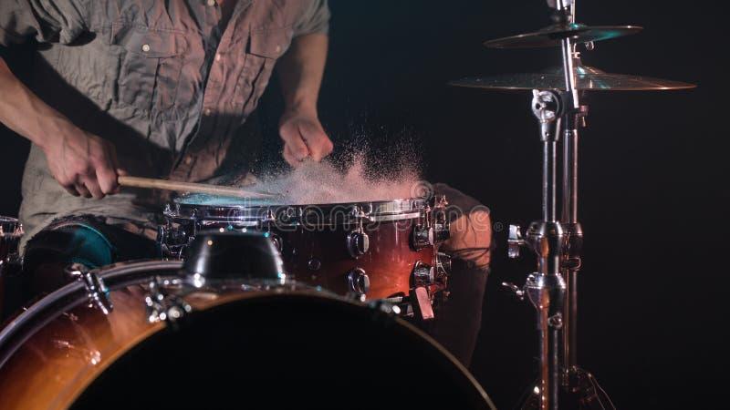 Der Musiker, der Trommeln mit spielt, spritzt, schwarzer Hintergrund mit schönem weichem Licht lizenzfreie stockbilder