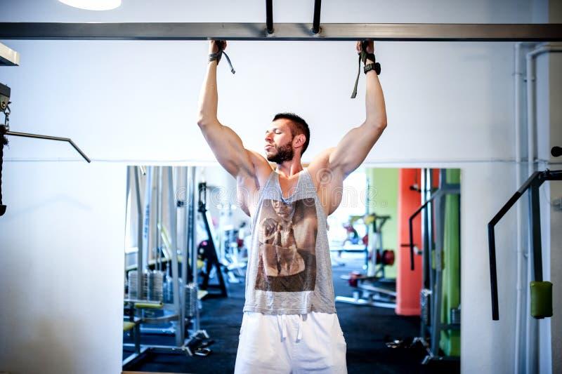 Der muskulöse sexy Mann, der an der Turnhalle ausarbeitet, Kinn ups stockbilder