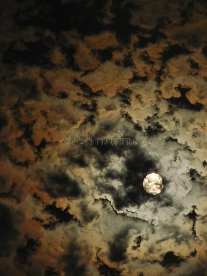 Der nächtliche Himmel und ein heller Vollmond unter mystischen Wolken stockbilder