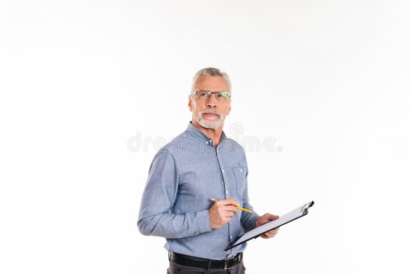 Der nachdenkliche bärtige, beim Halten des Ordners oben schauende und denkende Mann lokalisierte lizenzfreie stockfotografie