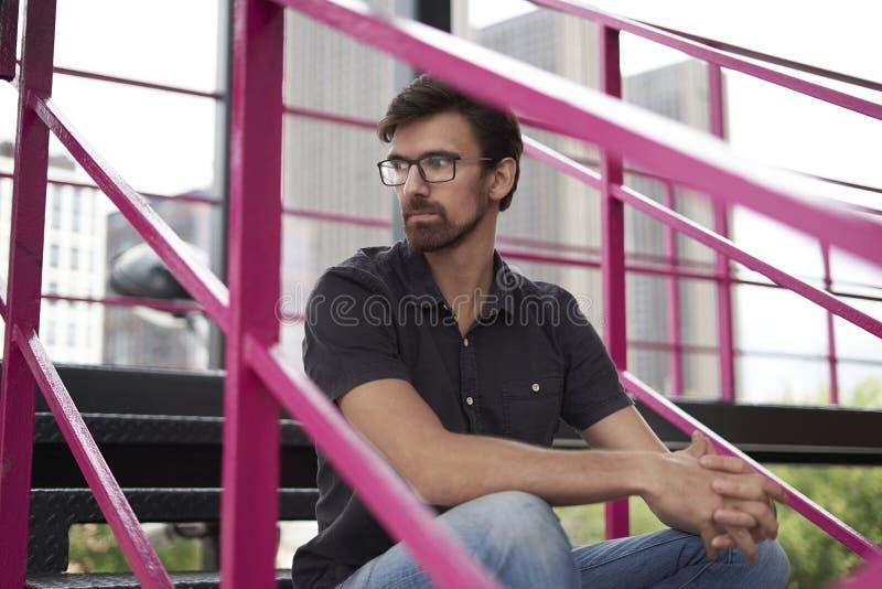 Der nachdenkliche hübsche Kerl, der auf der Treppe trägt Gläser sitzt, schauen nach links Stadtansichtgebäude hinten lizenzfreie stockfotografie