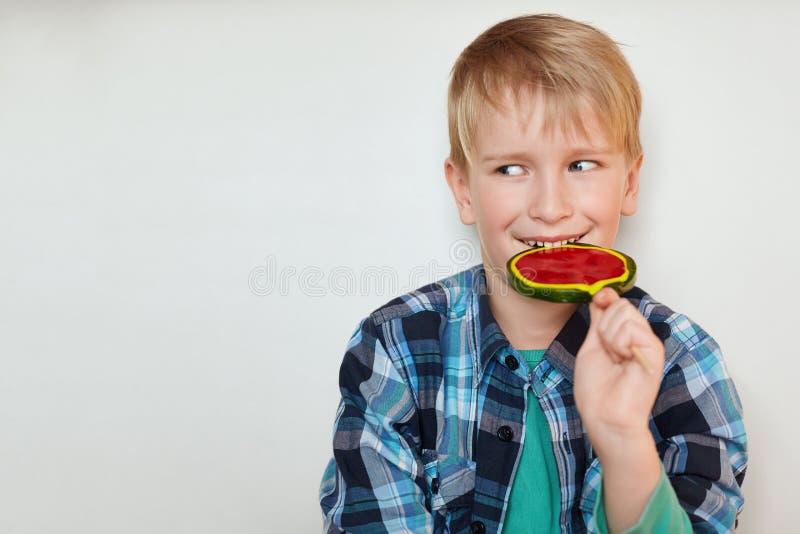 Der nette blonde Junge mit blauen Augen kleidete in überprüftem Hemd den Lutscher leckend an, der den glücklichen Ausdruck hat, d lizenzfreie stockfotografie