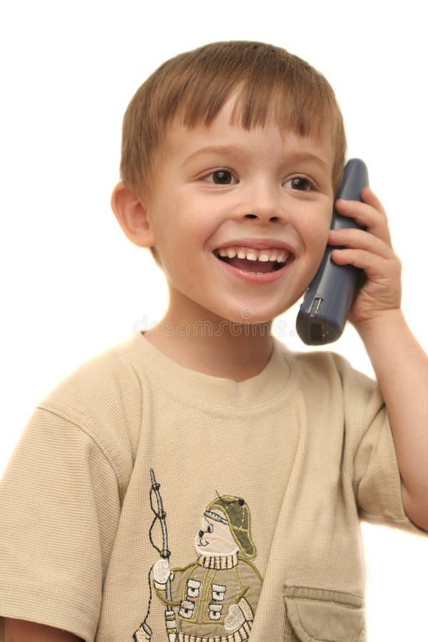 Der nette Junge spricht durch Telefon stockfotografie