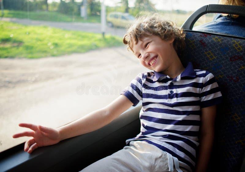 Der nette kleine Junge in einem gestreiften T-Shirt fährt mit dem Bus stockfotografie