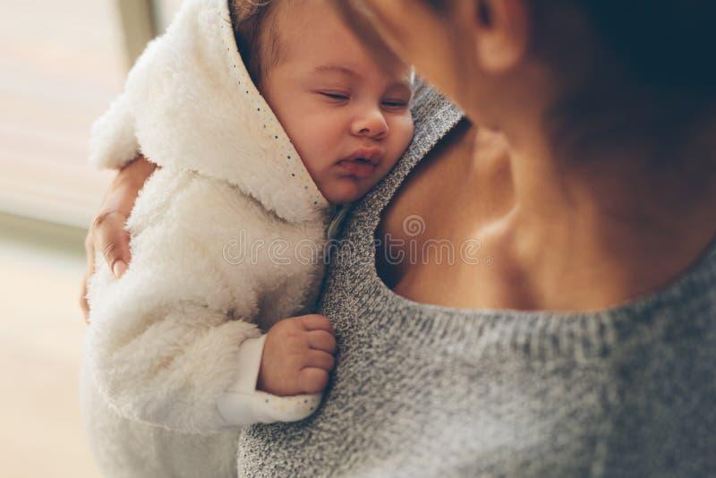 Der nette kleine Junge, der in seinem Mutter ` s schläft, bewaffnet stockbild