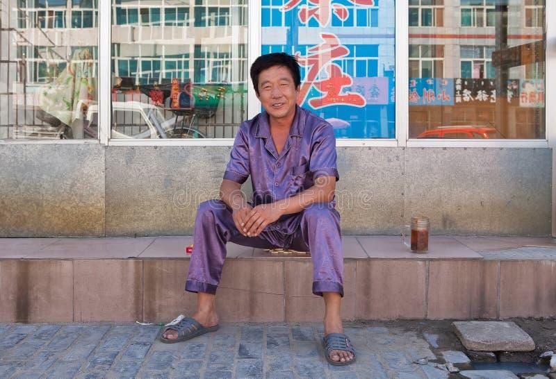 Der nette Mann, der im Pyjama gekleidet wird, sitzt außerhalb seines Hauses, Tongliao, China lizenzfreie stockfotos