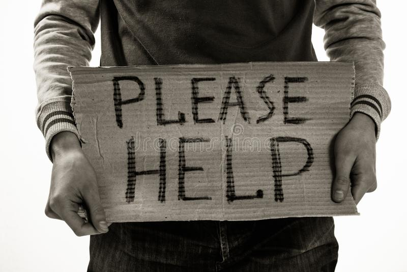 Der obdachlose arme Mann, der Kartonbrett mit Wort helfen hält bitte stockbild