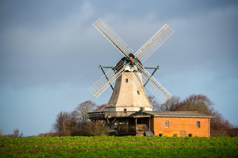 In der offenen Natur auf einem Gebiet steht eine Windmühle stockfoto