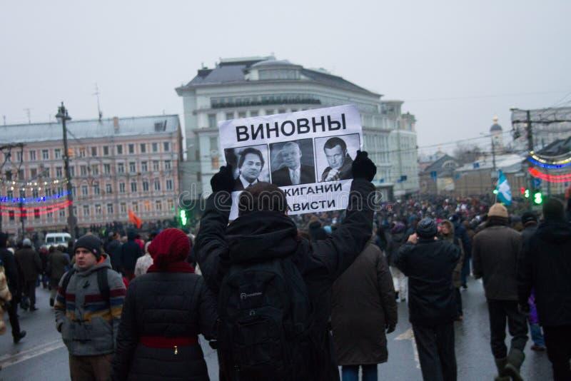 Der Oppositionist trägt das Plakat, in dem Nemtsovs Mordes die Spitzenbeamten der russischen Propaganda Fernsehkanäle beschuldigt stockbild