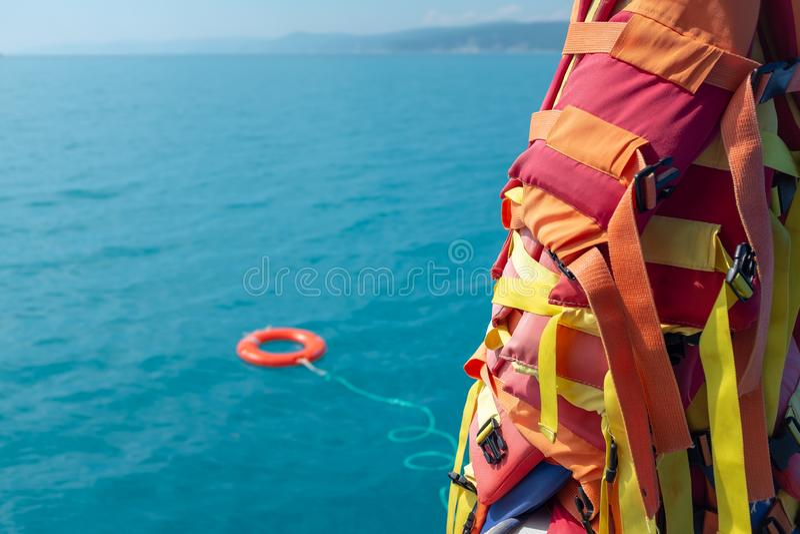 Der orangefarbene Rettungsring wird in das blaue Meer vor dem hintergrund der Lebensrettung geworfen stockfotos