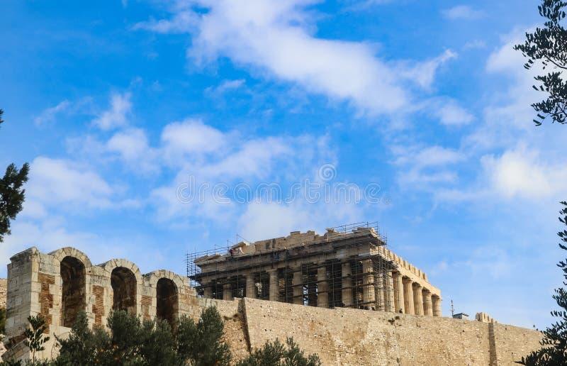 Der Parthenon unter Erneuerung auf der Akropolise von Athen Griechenland mit dem Odeon von Herodes-Atticus - Steintheaterstruktur lizenzfreie stockfotos
