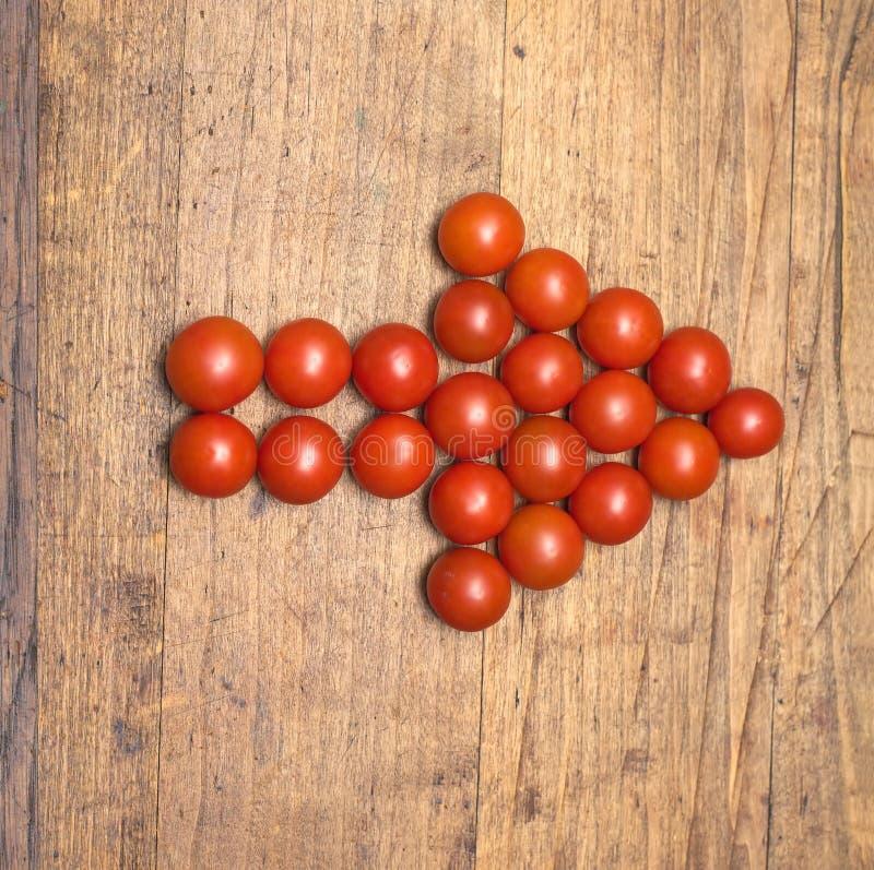Der Pfeil der richtigen Richtung, der von vielen reifen roten Tomaten errichtet wird, liegt Nahaufnahme lizenzfreie stockfotos