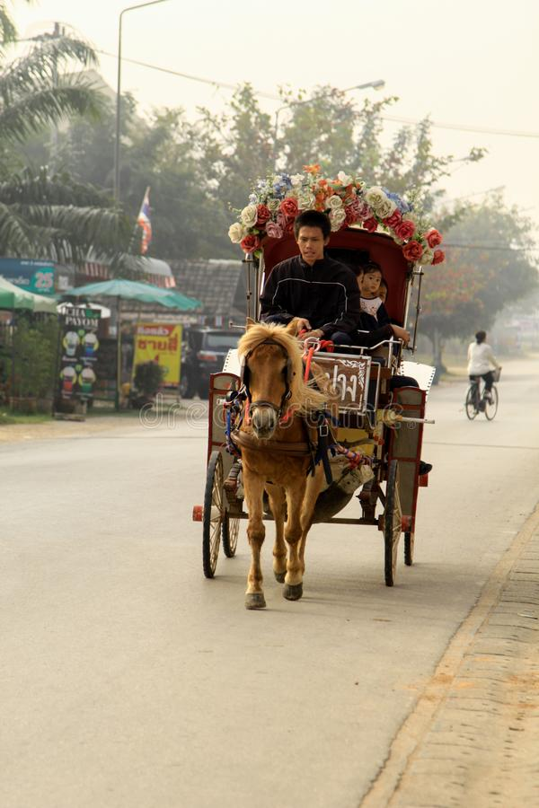 Der Pferdewagen mit Leuten in Lampang bei Wat Phra That Lampa stockbild