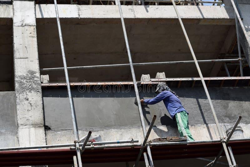 Der philippinische Baumaurer, der Bewurf an Bord des Baugerüsts vergipst, leitet auf hohes Gebäude allein lizenzfreies stockbild