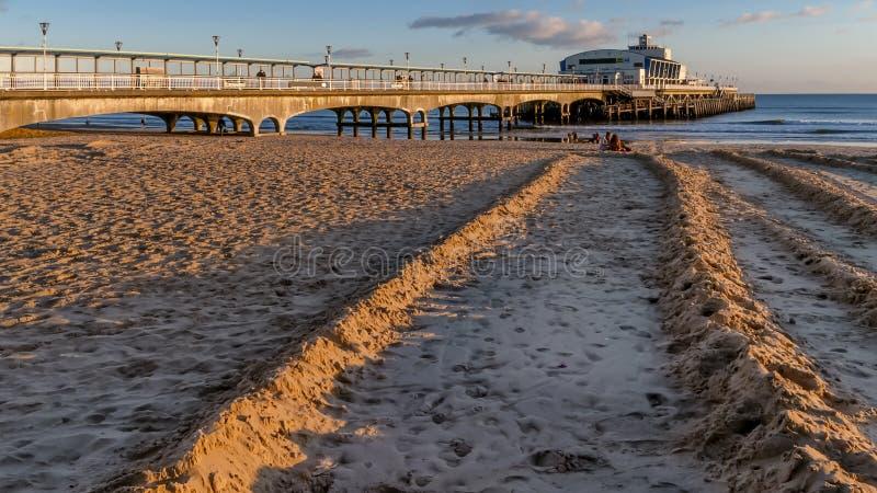 Der Pier und der sandige Strand von Bournemouth angesichts eines schönen Sonnenuntergangs, England stockbild