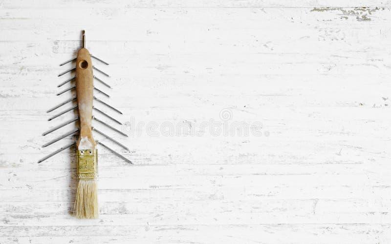 Der Pinsel und Nägel, die als Weihnachtsbaum auf einem Weiß verziert werden, flehen an lizenzfreie stockfotografie