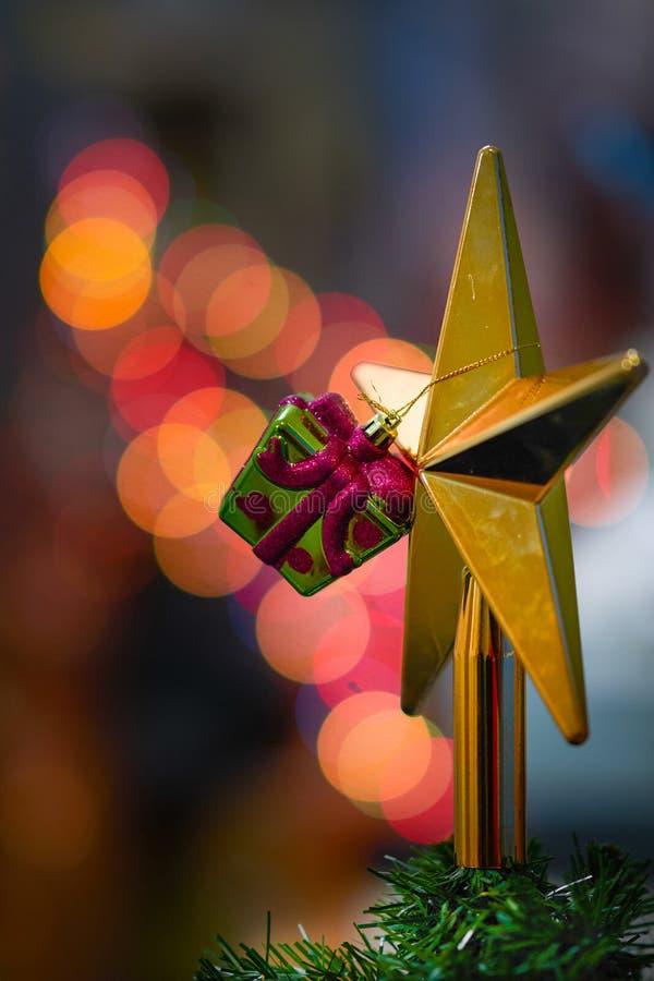 Der Plastik, der wie Dekors vorhanden ist, hängt am goldenen Stern an für Baum und lizenzfreies stockbild