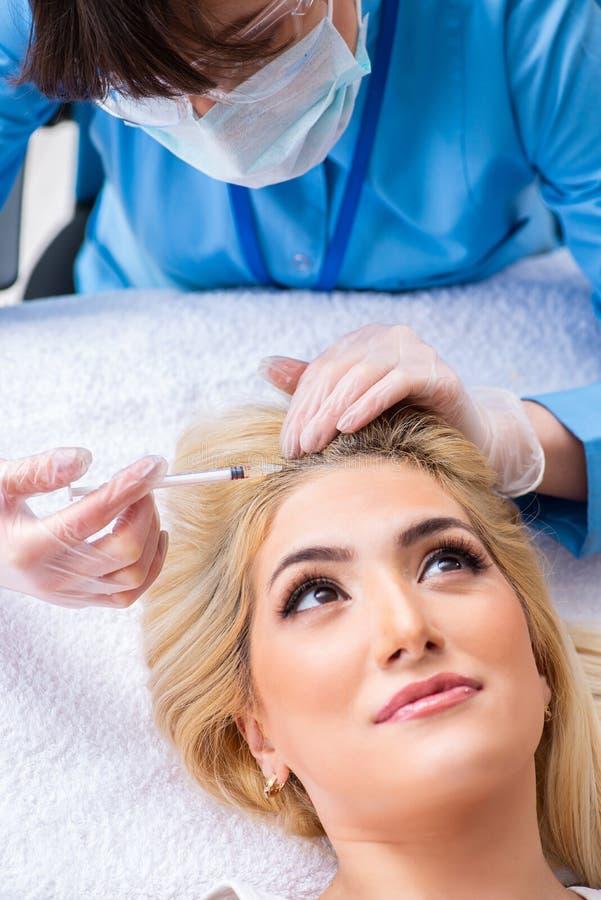 Der plastische Chirurg, der für Operation auf Frauenhaar sich vorbereitet lizenzfreies stockfoto