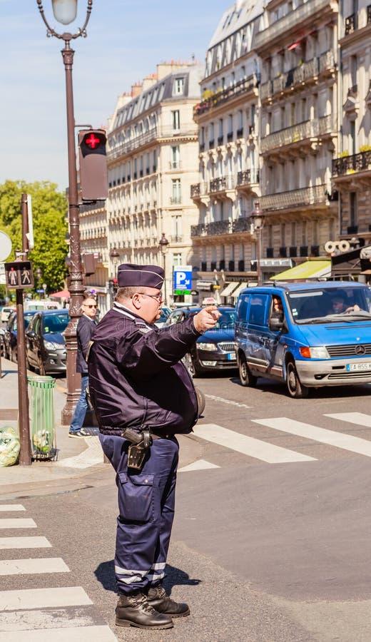Der Polizist handhabt den Transport an den Kreuzungen von Paris stockfotografie