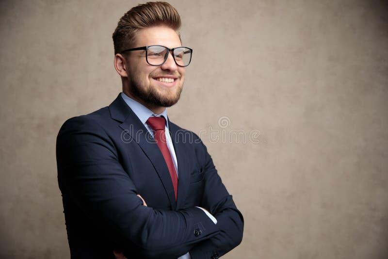 Der positive Geschäftsmann, der mit seiner Hand lächelt, faltete sich lizenzfreies stockbild